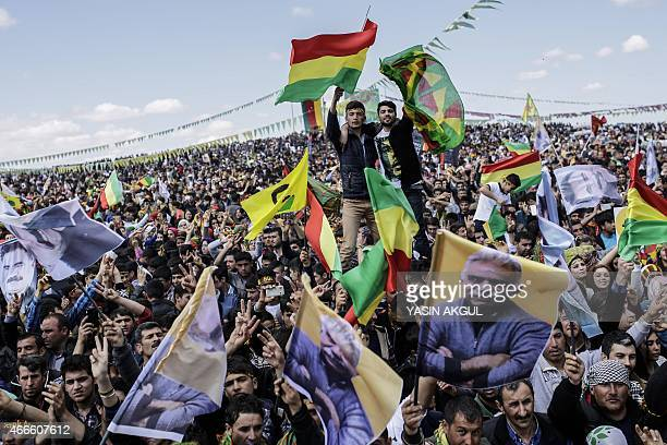 People wave Kurdish flags and flags bearing the portrait of jailed Kurdish leader Abdullah Ocalan as they celebrate Newroz which marks the arrival of...