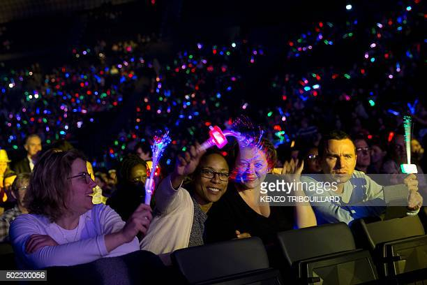 People wave lighted fiber optic wands as they attend a concert to thank the anonymous 'heroes' who assisted victims of the November 13 Paris attacks...