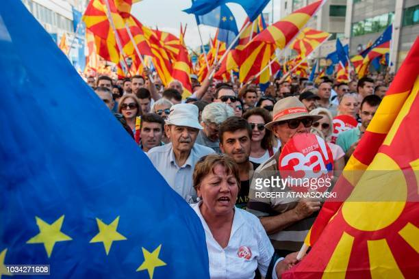 People wave Macedonian and Europan flags as they attend a campaign rally for the yes ahead of a referendum on wether to change the country's name to...