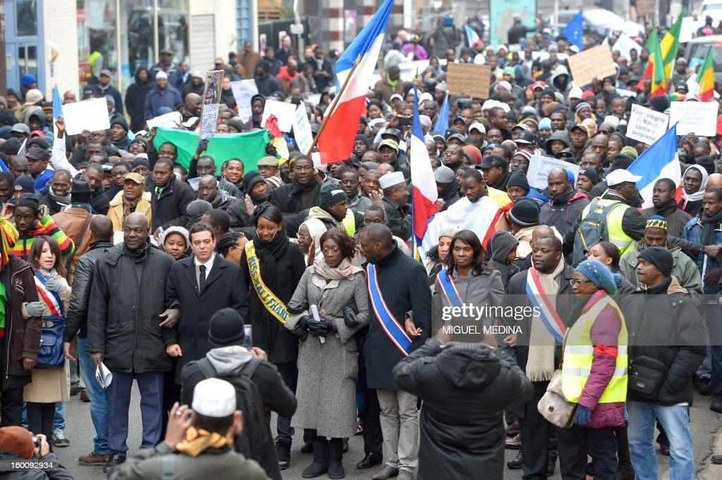 People wave Malian and French flags during a demonstration, organized by Malian associations, in support of the liberation forces of Mali on January 26, 2013 in Montreuil, near Paris. Placard reads 'For a united Mali, against terrorism'.