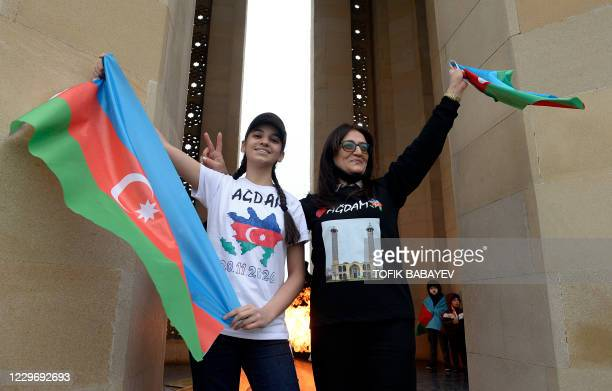 People wave national flags as they celebrate the country's victory over Armenia after a weeks-long war over the disputed Nagorno-Karabakh region in...