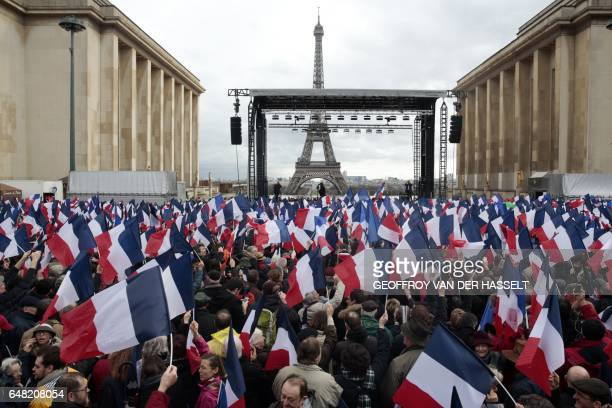 People wave national flags during a rally to support French presidential election candidate for the rightwing Les Republicains party Francois Fillon...