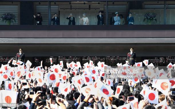 People wave national flags to celebrate the 84th birthday of Japan's Emperor Akihito at the Imperial Palace in Tokyo on December 23 as other members...