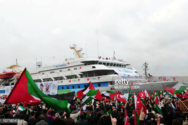 People wave Palestinian and Turkish flags as they welcome the Mavi Marmara ship at Istanbul's Sarayburnu port on December 26 2010 The Turkish ferry...