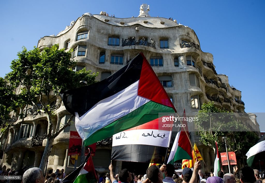 People wave palestinian flags as they pass by La Pedrera house during a demonstration anti-Israel in Barcelona on June 5, 2010 following a deadly Israel military raid Gaza-bound flotilla of aid ships on May 31. Spain, which holds the rotating EU presidency, condemned the Israeli army's raid on aid ships bound for Gaza and summoned Israel's ambassador.