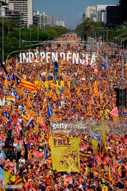 People wave proindependence Catalan flags 'Esteladas' while holding letters reading independence during a proindependence demonstration in Barcelona...