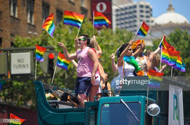 People wave rainbow flags on a float as it travels along the parade route of San Francisco's Gay Pride festival on June 2013 AFP PHOTO / JOSH EDELSON