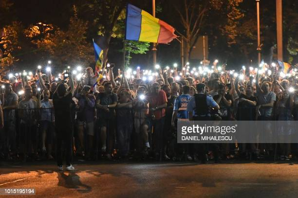 People wave Romanian national flags during a demonstration to protest against the government on August 11 in front of the government's headquarters...