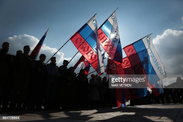 TOPSHOT People wave Russian national flag as they celebrate the third anniversary of the annexation of the Crimea by the Russian Federation in...