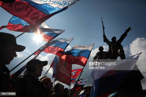 People wave Russian national flag as they celebrate the third anniversary of the annexation of the Crimea by the Russian Federation in Sevastopol on...