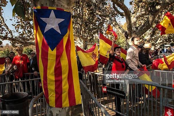 People wave Spanish flags as they protest next to a ProIndependence Catalan flag outside the Parliament of Catalonia during a parliamentary session...