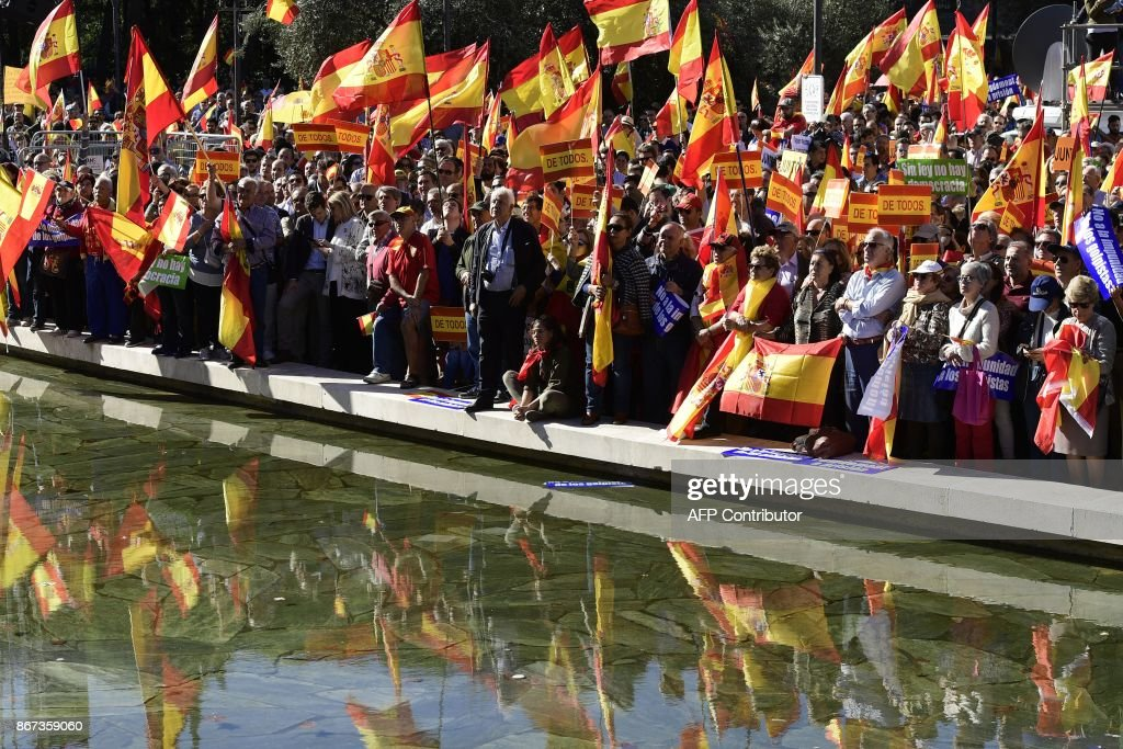 People wave Spanish flags during a demonstration calling for unity at Plaza de Colon in Madrid on October 28, 2017, a day after direct control was imposed on Catalonia over a bid to break away from Spain. Spain moved to assert direct rule over Catalonia, replacing its executive and top functionaries to quash an independence drive that has plunged the country into crisis and unnerved secession-wary Europe. /