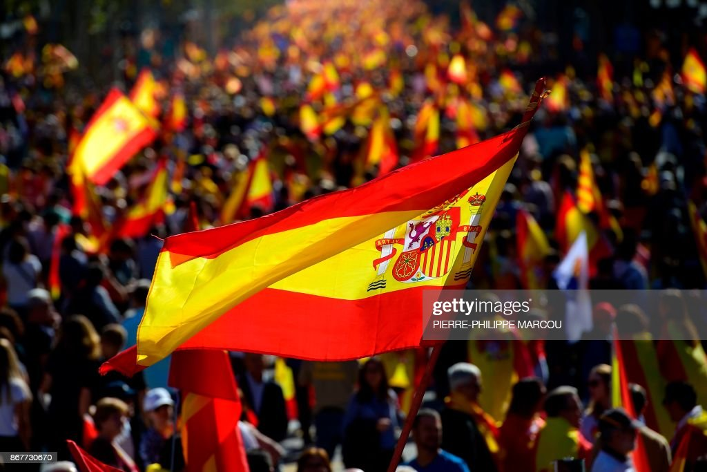 People wave Spanish flags during a pro-unity demonstration in Barcelona on October 29, 2017. Pro-unity protesters were to gather in Catalonia's capital Barcelona, two days after lawmakers voted to split the wealthy region from Spain, plunging the country into an unprecedented political crisis. /
