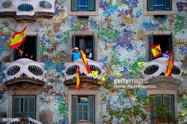 People wave Spanish flags from the Casa Batllo during a prounity demonstration in Barcelona on October 29 2017 Prounity protesters were to gather in...