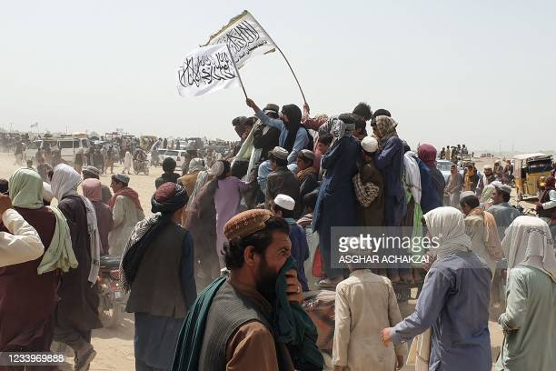 People wave Taliban flags as they drive through the Pakistani border town of Chaman on July 14 after the Taliban claimed they had captured the Afghan...