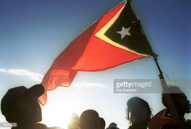 People wave the East Timorese flag during independence day celebrations May 19 2002 in Dili East Timor East Timor formally declared independence and...
