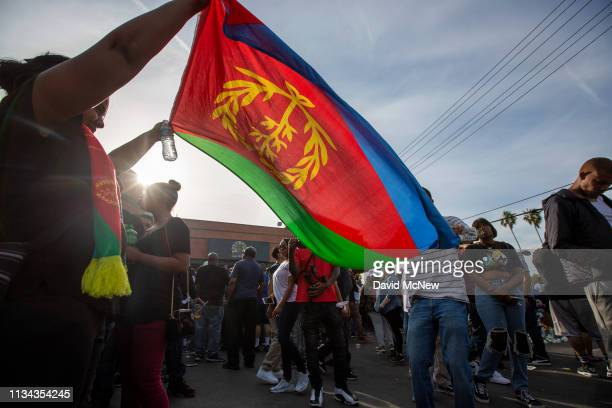 People wave the flag of Eritrea in honor of the original home of rapper Nipsey Hussle as they gather to mourn him on April 1 2019 in Los Angeles...