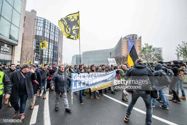 People wave the flag of the Flanders as they take part in a gathering called by the right-wing Flemish party Vlaams Belang and other organisations,...
