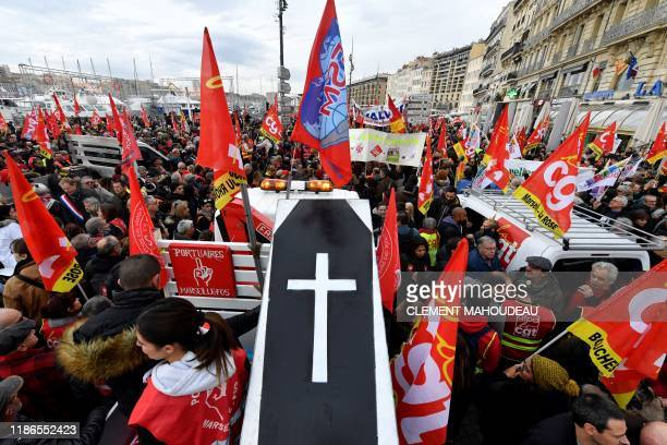 TOPSHOT People wave the flags of French trade union General Confederation of Labour and carry a mocked coffin as they take part in a demonstration to...