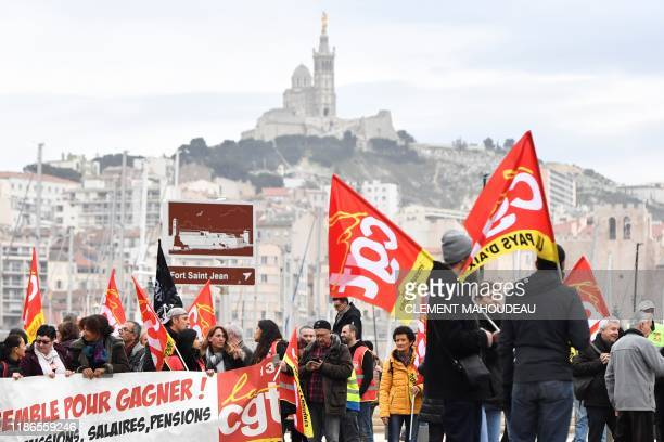 People wave the flags of French trade union General Confederation of Labour with the NotreDame de la Garde in the background during a demonstration...