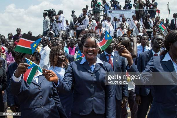 People wave the national flags of South Sudan during a peace ceremony in Juba South Sudan on October 31 2018 South Sudan rebel leader Riek Machar...