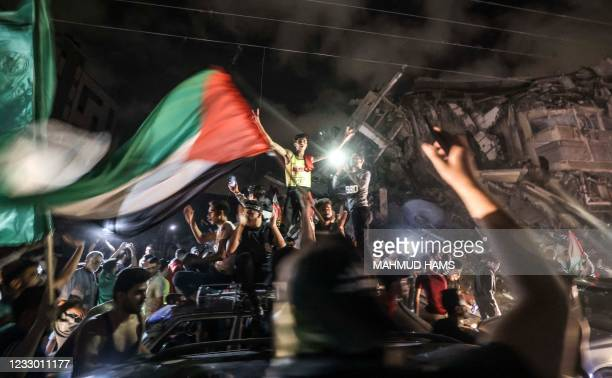 People wave the Palestinian flag as they celebrate in front of a destroyed building in Gaza City early on May 21 following a ceasefire brokered by...
