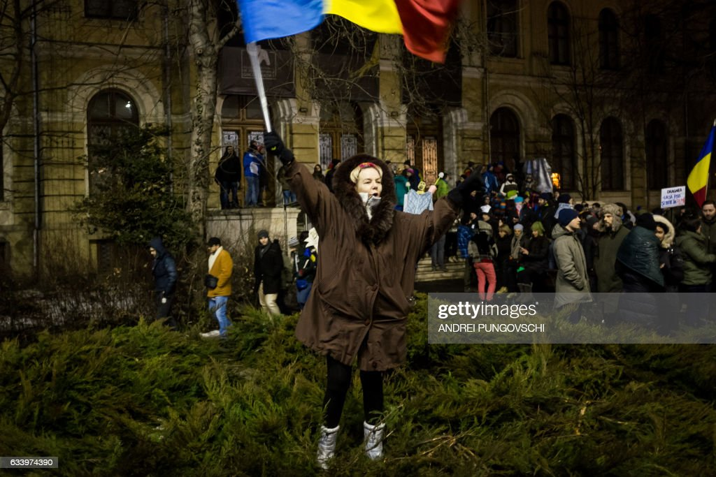 People wave their national flag as they protest against their government in Bucharest on February 5, 2017. Romania's government formally repealed contentious corruption legislation that has sparked the biggest protests since the fall of dictator Nicolae Ceausescu in 1989, ministerial sources said. The emergency decree, announced on Tuesday (January 31, 2017), would have decriminalised certain corruption offences, raising concerns in Romania and outside that the government was easing up on fighting graft. Centre-right President Klaus Iohannis, elected in 2014 on an anti-graft platform, previously had called the decree 'scandalous' and moved to invoke the constitutional court. / AFP / ANDREI
