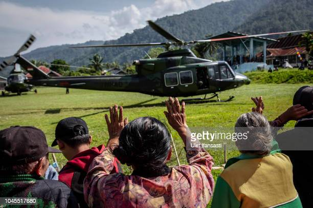 People wave to a army helicopter after transporting logistic in isolated village of Kulawi following the earthquake on October 4, 2018 in Sigi,...