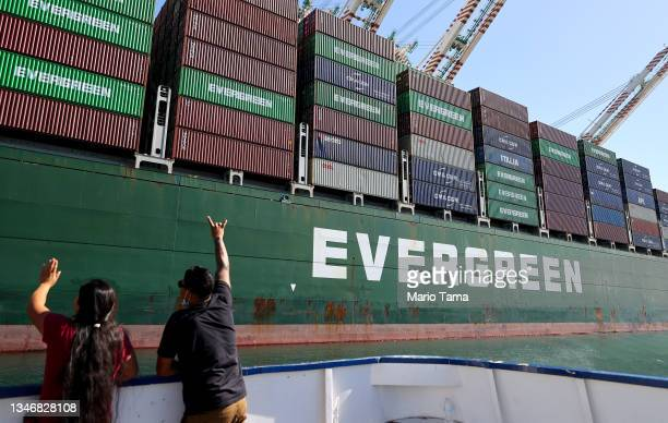 People wave to a worker aboard a container ship as they ride on a tour boat at the Port of Los Angeles, the nation's busiest container port, on...