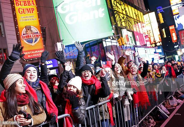 People wave to the Jumbotron camera in the leadup to New Year's eve celebrations in Times Square in New York City on December 31 2016 Security...