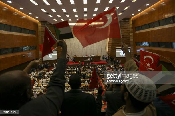 People wave Turkish and Sudanese flags during a meeting where President of Turkey Recep Tayyip Erdogan receives the title of honorary PhD from the...