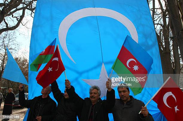 People wave Turkish Azerbaijan and a giant Uighur Turks flag in Ankara on February 26 2012 during a protest to commemorate the 20th anniversary of...
