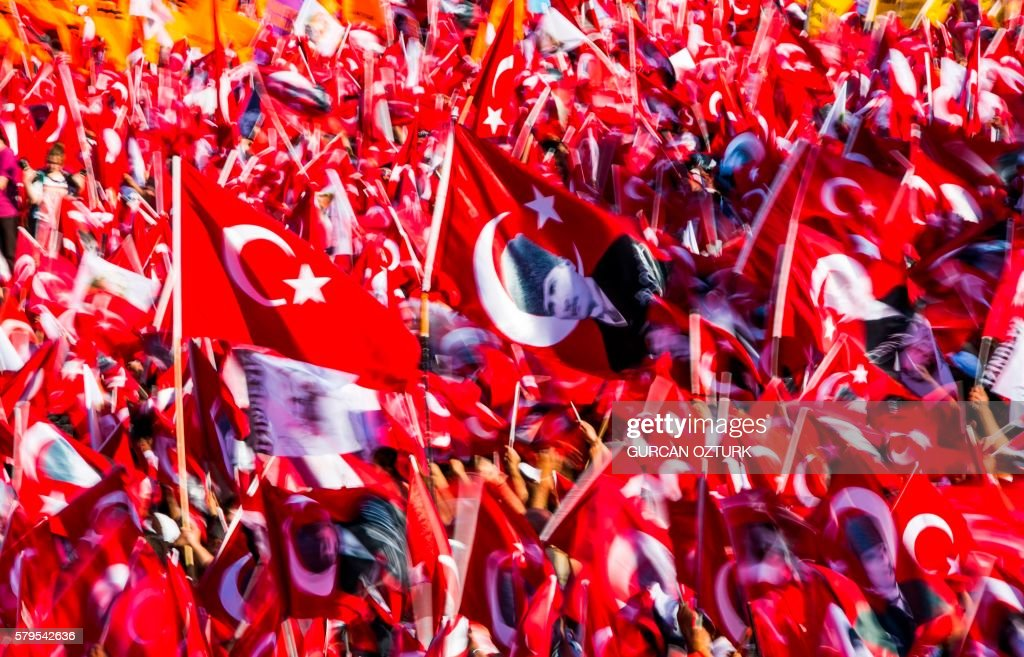 TOPSHOT - People wave Turkish flags and portraits of modern Turkey's founding father Mustafa Kemal Ataturk, during a rally organised by the main opposition group, the secular and centre-left Republican People's Party (CHO), on July 24, 2016 in Istanbul's Taksim square. - Many thousands of flag-waving Turks massed on July 24, 2016 for the first cross-party rally to condemn the coup attempt against President Recep Tayyip Erdogan, amid an ongoing purge of suspected state enemies. Istanbul's Taksim square was transformed into a sea of red national flags in what was dubbed a 'democracy festival'. But in stark contrast to the celebratory and patriotic mood in Istanbul, human rights group Amnesty International in London claimed it had 'credible evidence' of the beating and torture of detainees.