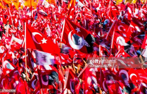 People wave Turkish flags and portraits of modern Turkey's founding father Mustafa Kemal Ataturk, during a rally organised by the main opposition...