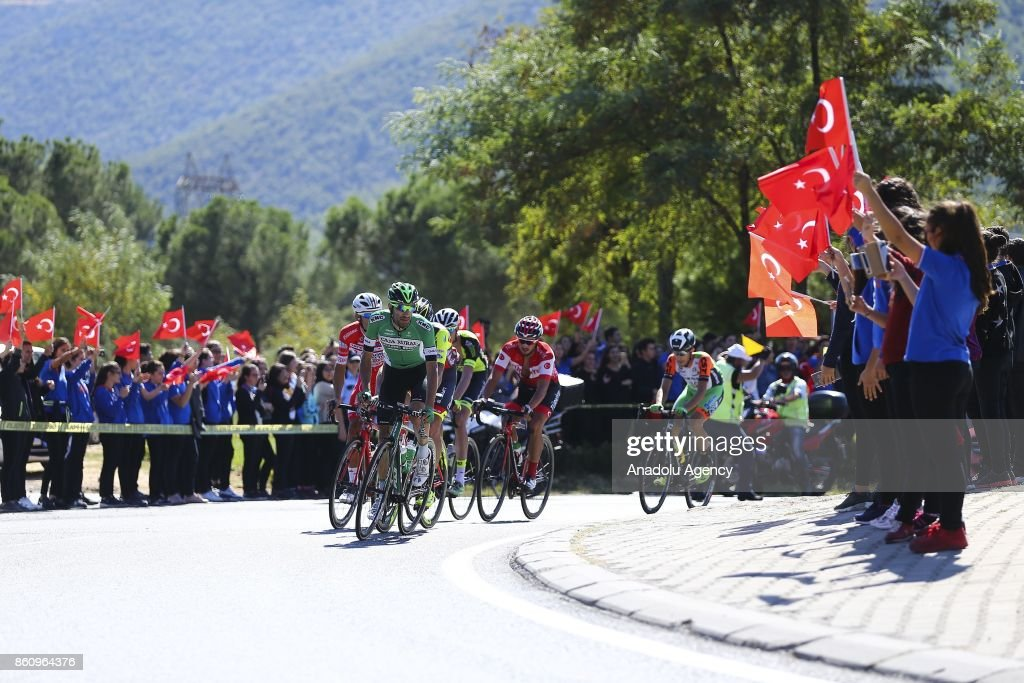 People wave Turkish flags as cyclists compete in 204,1