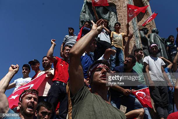 People wave Turkish flags as they stand around the Republic Monument in Taksim Square July 16 2016 in Istanbul Turkey Istanbul's bridges across the...