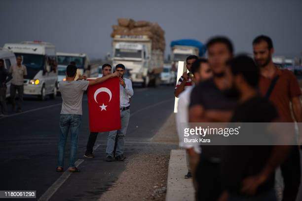 People wave Turkish flags as Turkish soldiers prepare to cross the border into Syria on October 09 2019 in Akcakale Turkey The military action is...