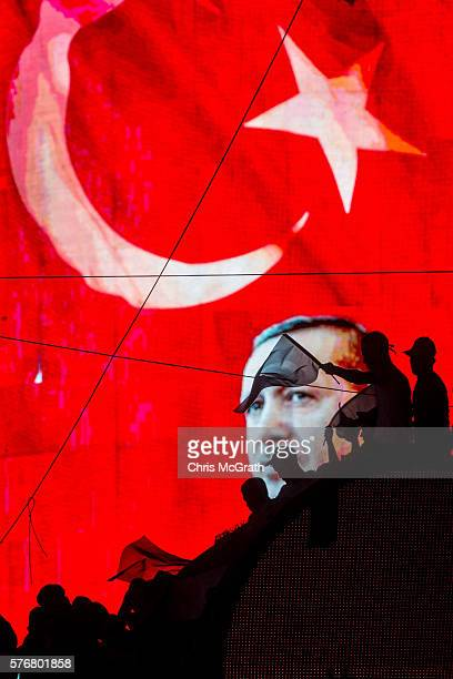 People wave Turkish flags in front of an electronic billboard displaying the face of President Recep Tayyip Erdogan at a rally on the streets of...