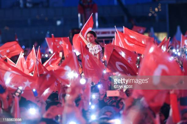 People wave Turkish national flags as they stand at the Ataturk International Airport in Istanbul on July 15, 2019. - Turkey commemorates, on July...