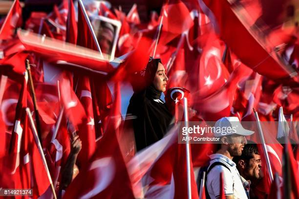 TOPSHOT People wave Turkish national flags as they stand near the 'July 15 Martyrs Bridge' in Istanbul on July 15 2017 Turkey is marking one year...