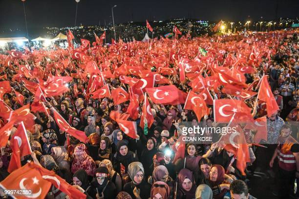People wave Turkish national flags as they stand near the July 15 Martyrs Bridge in Istanbul on July 15 2018 Turkey on commemorated the second...