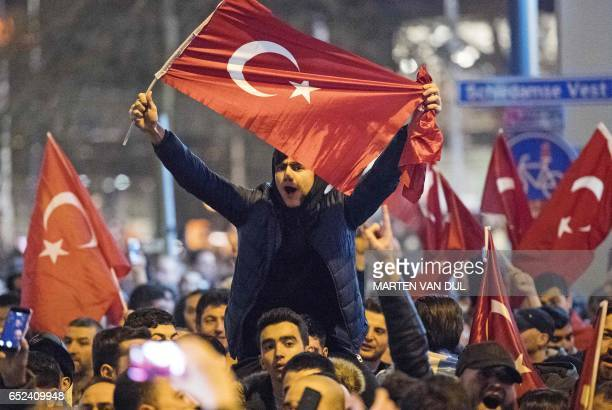 People wave Turkish national flags during a demostration near the Turkish consulate in Rotterdam on March 11 2017 after the Turkish Family Minister...