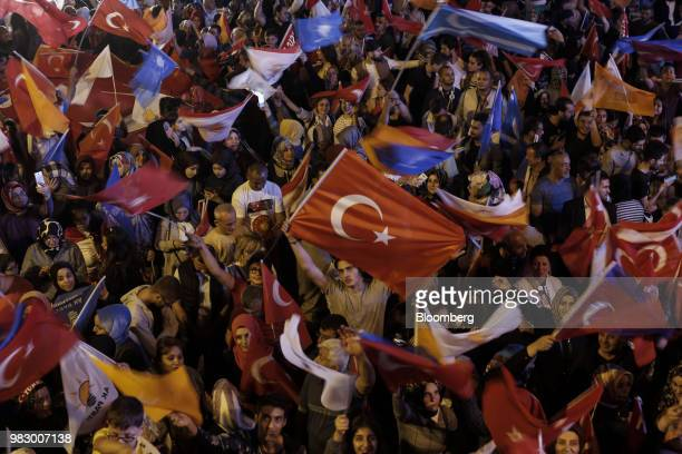People wave Turkish national flags outside of the AKP party headquarters as they react to the outcome of the parliamentary and presidential elections...