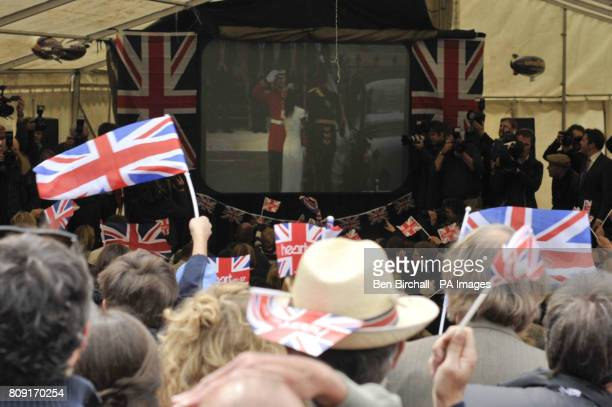 People wave Union flags and cheer as they see Catherine Middleton arrive at Westminster Abbey as they watch the live TV broadcast on a screen in a...