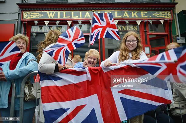 People wave Union Jack flags as Queen Elizabeth II and Prince Philip Duke of Edinburgh arrive to visit Macartin's Cathedral on June 26 2012 in...