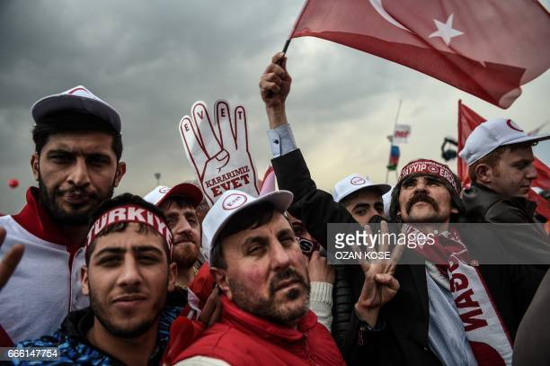 People wave 'YES' banners and Turkish national flags on April 8 2017 during a Campaign rally for the 'yes' to a constitutional referendum in Istanbul...