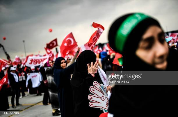 People wave 'YES' banners and Turkish national flags on April 8 2017 during a campaign rally for the 'yes' vote in a constitutional referendum in...