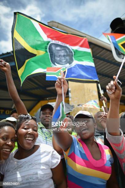 People waves flags as they gather in Mthatha waiting for the funeral cortege of former South African president Nelson Mandela to pass by on its way...