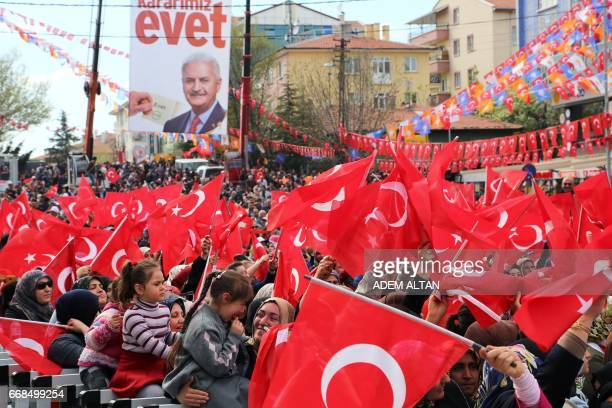 People waves Turkish flags in the Etimesgut district of Ankara on April 14 as they attend a 'yes' campaign rally with the Turkish prime minister...