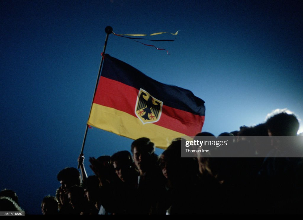 People waving a German Flag on German Unity Day on October 03, 2014, in Berlin, Germany. The year 1990 marks the 25th anniversary of the fall of the Berlin Wall.